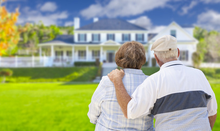 selling house: Happy Senior Couple From Behind Looking at Front of House. Stock Photo