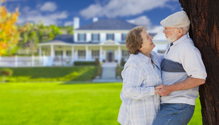 selling house: Happy Senior Couple in the Front Yard of Their House.