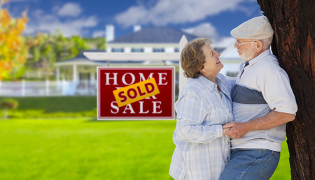 Sold Real Estate Sign with Happy Affectionate Senior Couple Hugging in Front of House. photo
