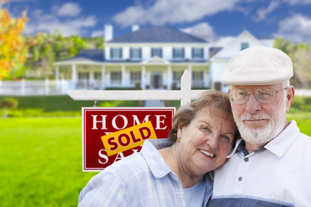 Happy Affectionate Senior Couple Hugging in Front of Sold Real Estate Sign and House. Stock Photo