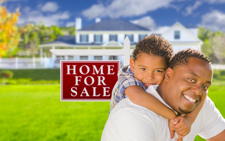 Happy Mixed Race Father and Son In Front of For Sale Real Estate Sign and New House. photo