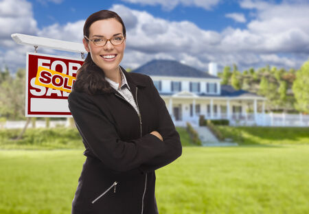 Attractive Mixed Race Woman in Front of House and Sold Real Estate Sign. photo