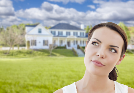 Thoughtful Pretty Mixed Race Woman In Front of House Looking up and to the Side. 版權商用圖片