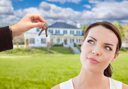 Real Estate Agent Hainds Thoughtful Pretty Mixed Race Woman Keys In Front of House. photo