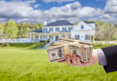 cash on hand: Handing Over Cash For House in Front of Beautiful New Home.