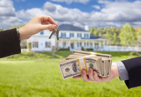 Handing Over Cash For House Keys in Front of Beautiful New Home. Stock Photo