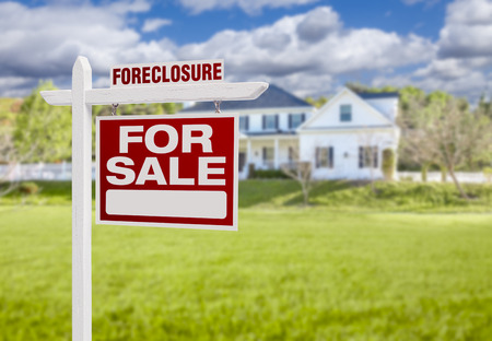 Foreclosure Home For Sale Real Estate Sign in Front of Beautiful Majestic House. Stock Photo