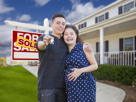property for sale: Happy Hispanic Couple In Front of New Home And Sold Real Estate Sign Showing Off Their House Keys.