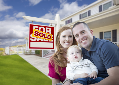 Happy Young Military Family in Front of Sold Real Estate Sign and New House. photo