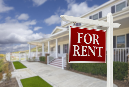 Red For Rent Real Estate Sign in Front of Beautiful House. photo