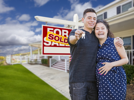 Happy Hispanic Couple In Front of New Home And Sold Real Estate Sign Showing Off Their House Keys.