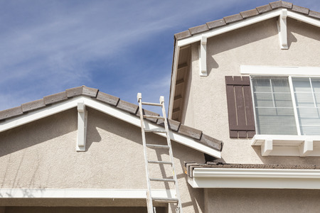 property ladder: Construction Ladder Leaning Up Against A Freshly Painted House.