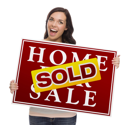 homebuyer: Happy Mixed Race Female with Sold Home For Sale Real Estate Sign Isolated on White.