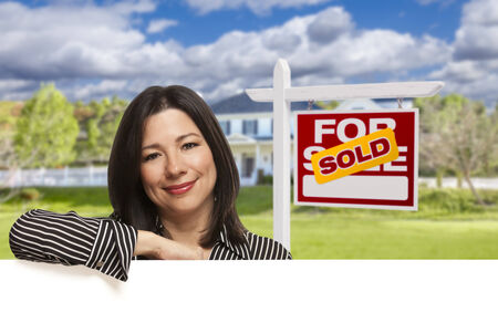 homebuyer: Pretty Hispanic Woman Leaning on White in Front of Beautiful House and Sold For Sale Real Estate Sign.