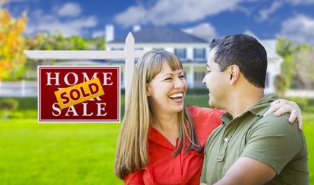 mixed race couple: Feliz pareja de raza mixta delante de Home vendido para venta inmobiliaria signo y casa. Foto de archivo