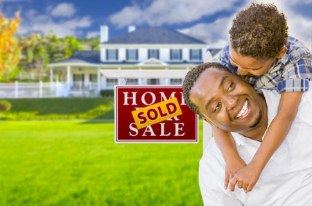7 9 years: Happy Mixed Race Father and Son In Front of Sold Real Estate Sign and New House. Stock Photo
