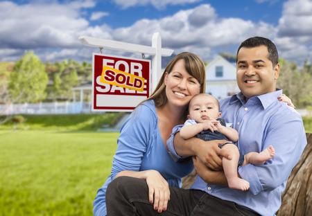 Feliz de la raza mezclada joven de la familia delante del hogar vendido para venta inmobiliaria signo y casa. Foto de archivo