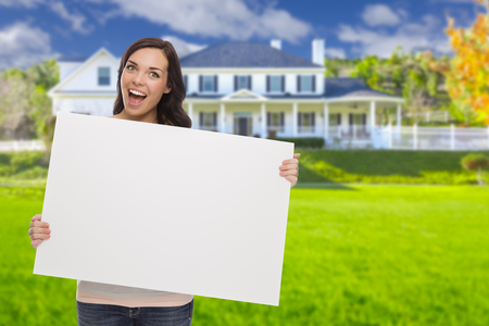 sell: Excited Mixed Race Female with Blank Sign In Front of Beautiful House.