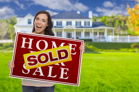 sales person: Excited Mixed Race Female with Sold Home For Sale Real Estate Sign In Front of Beautiful House.