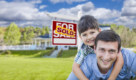 Mixed Race Father and Son Celebrating with a Piggyback in Front Their House and Sold Real Estate Sign. photo