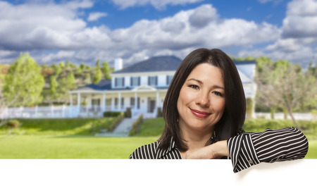 seller: Pretty Hispanic Woman Leaning on White in Front of Beautiful House.