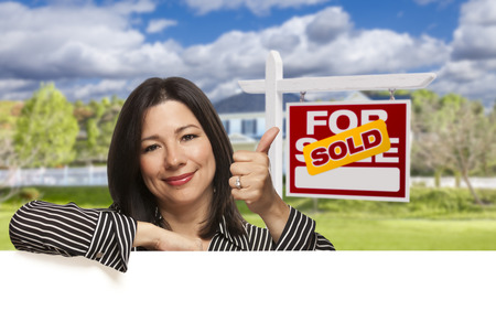 homebuyer: Pretty Hispanic Woman Leaning on White with Thumbs Up in Front of Beautiful House and Sold For Sale Real Estate Sign.