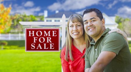 selling house: Happy Couple in Front of For Sale Real Estate Sign and New House.