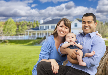 Happy Mixed Race Young Family in Front of Beautiful House. Stock Photo