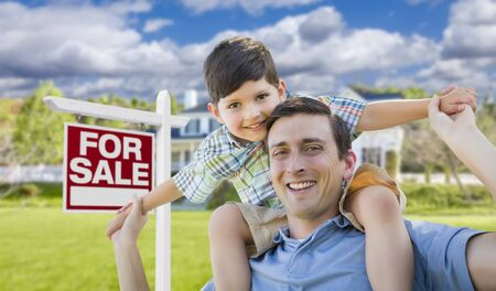 Mixed Race Father and Son Celebrating with a Piggyback in Front Their House and For Sale Real Estate Sign. photo