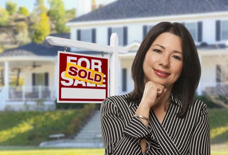 Orgulloso, atractivo hispanos agente femenina de vendido para venta inmobiliaria signo y casa. Foto de archivo