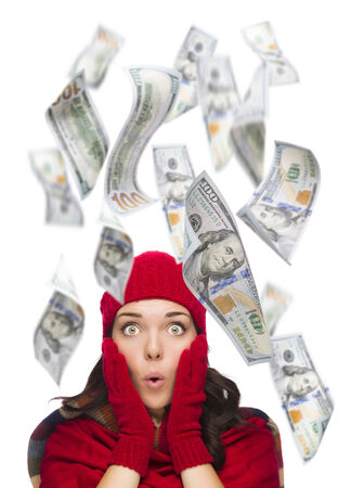warmly: Young Excited Warmly Dressed Woman with $100 Bills Falling Money Around Her on White. Stock Photo