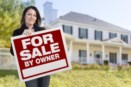sales person: Smiling Hispanic Female Holding For Sale By Owner Sign In Front of Beautiful House.