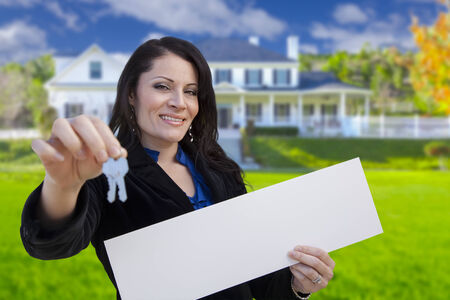homebuyer: Hispanic Woman Holding Blank Sign and Keys In Front of Beautiful House. Stock Photo