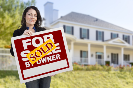 homebuyer: Smiling Hispanic Female Holding Sold For Sale By Owner Sign In Front of Beautiful House.
