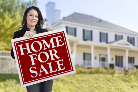 homebuyer: Smiling Hispanic Female Holding Sold For Sale Sign In Front of Beautiful House.