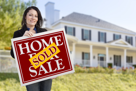 homebuyer: Smiling Hispanic Woman Holding Sold Home For Sale Sign In Front of Beautiful House. Stock Photo