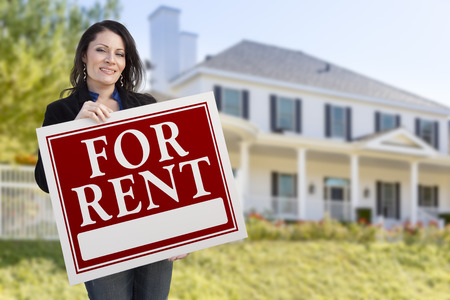 for rent sign: Smiling Hispanic Female Holding For Rent Sign In Front of Beautiful House.
