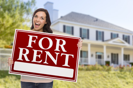renter: Excited Mixed Race Female Holding For Rent Sign In Front of Beautiful House.