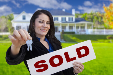 Hispanic Woman Holding Sold Sign and Keys In Front of Beautiful House. photo