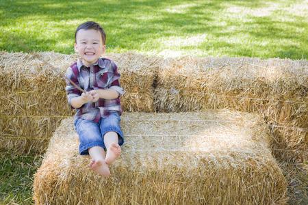 mixed race boy: Cute Young Mixed Race Boy Having Fun on Hay Bale Outside.