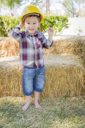 mixed race boy: Cute Young Mixed Race Boy Laughing with Hard Hat Outside Near Hay Bale. Stock Photo