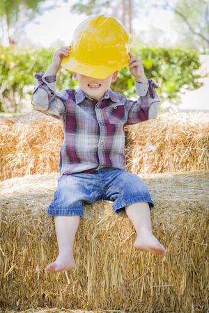 mixed race boy: Cute Young Mixed Race Boy Laughing with Hard Hat Outside Sitting on Hay Bale.