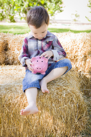 mixed race boy: Cute Young Mixed Race Boy Sitting on Hay Bale Putting Coins Into Pink Piggy Bank.