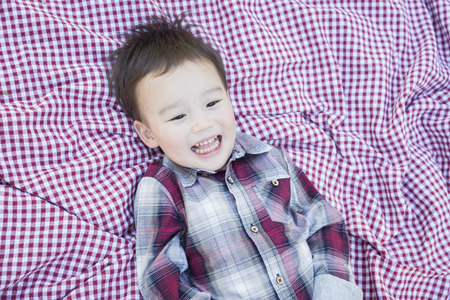 mixed race boy: Cute Young Mixed Race Boy Laughing On Picnic Blanket Outside.