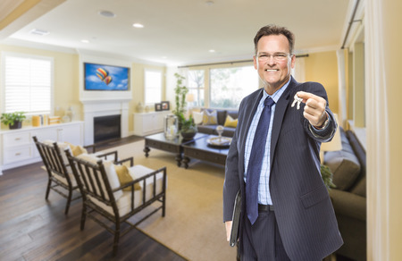 selling house: Smiling Male Real Estate Agent Handing Over Keys Standing in Beautiful Living Room.