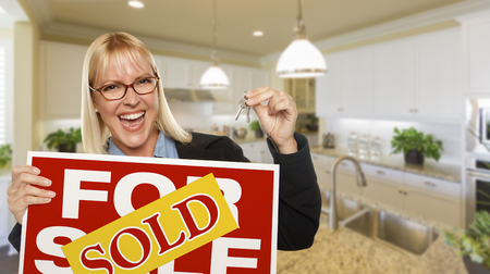 Happy Young Woman Holding Sold For Sale Real Estate Sign and Keys Inside Beautiful Custom Kitchen. photo
