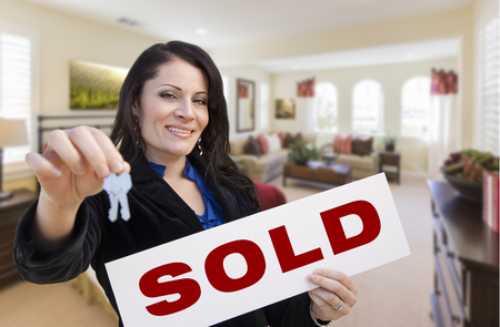 homebuyer: Happy Hispanic Woman with House Keys and Sold Sign in Beautiful Living Room.