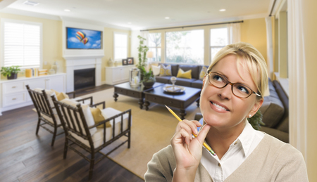 staging: Attractive Daydreaming Woman with Pencil Inside Beautiful Living Room. Stock Photo