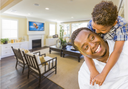 american house: Playful African American Father and Mixed Race Son in Living Room of House.