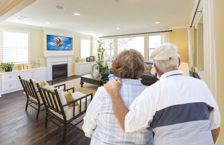 Affectionate Senior Couple Overlooking A Beautiful Custom Living Room. photo